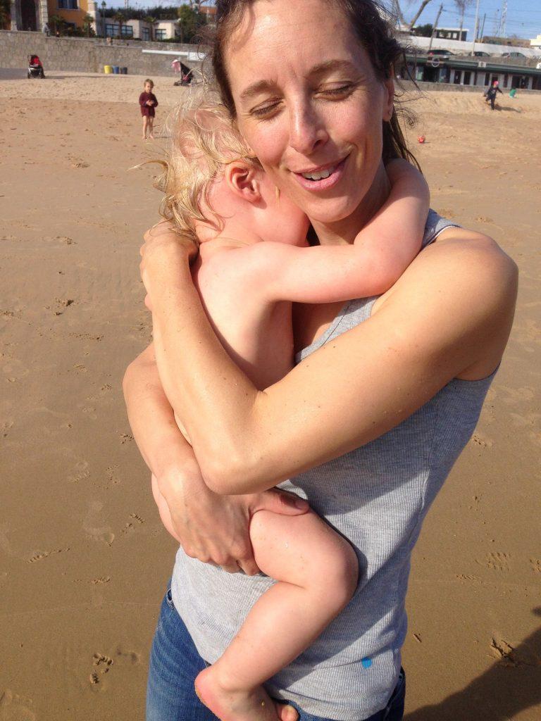 mama-holding-crying-baby-at-beach