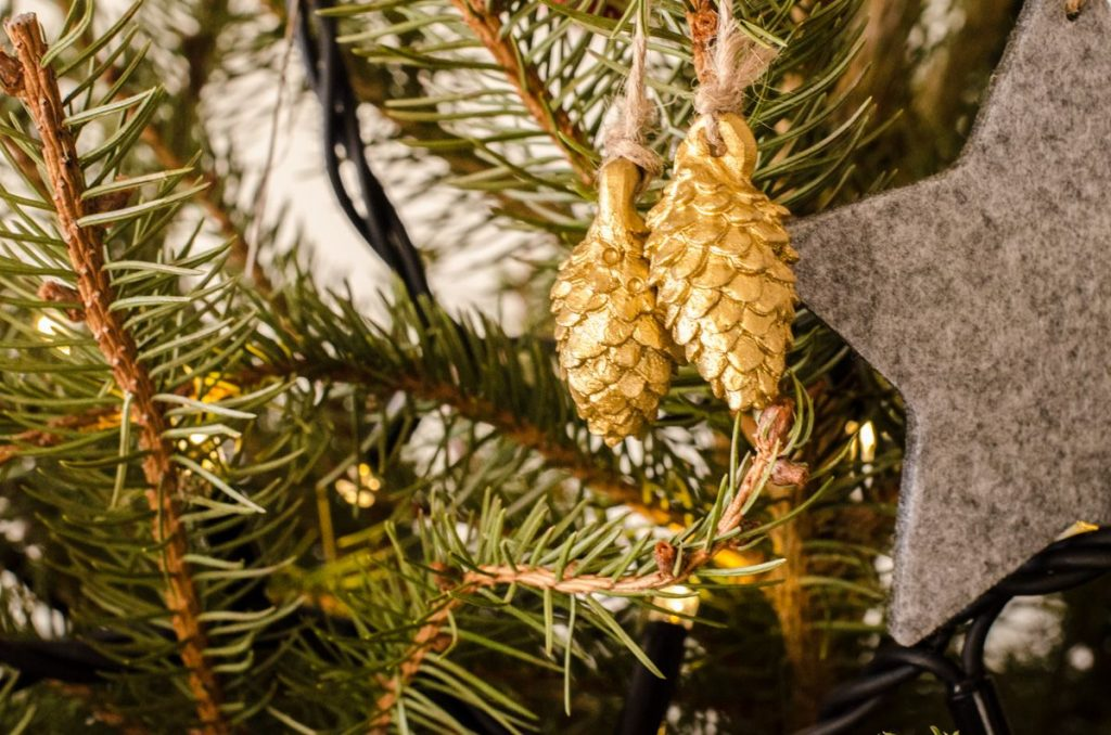 Golden pinecone ornaments on tree