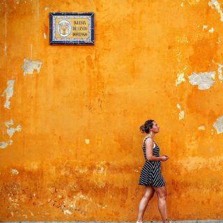 Woman walking in front of orange wall