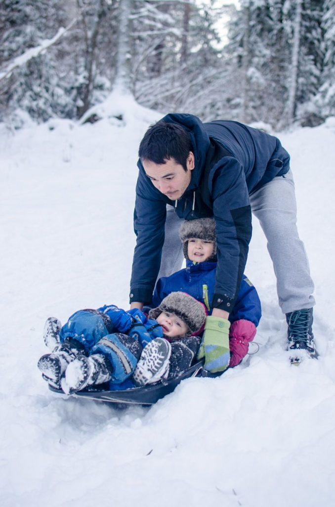 James pushing boys down sledding hill