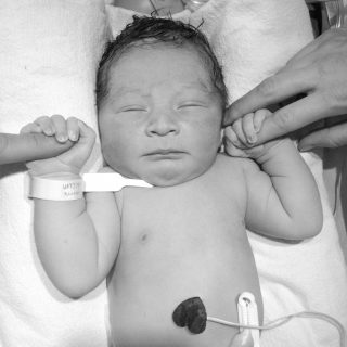Newborn baby holding parents' fingers