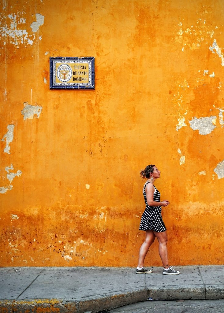 Woman walking in front of orange wall