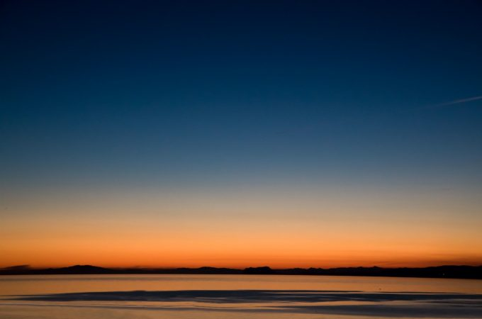 Blue and orange sky over water at sunrise