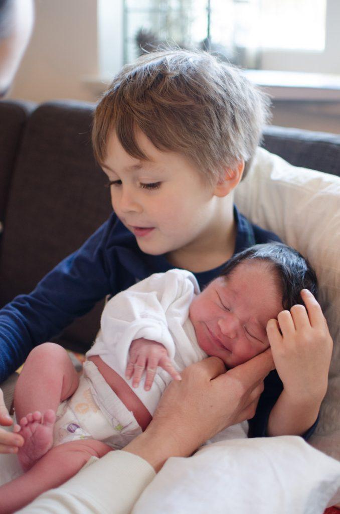 Big brother holding newborn