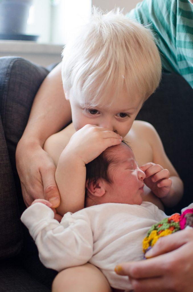 Big brother kissing newborn