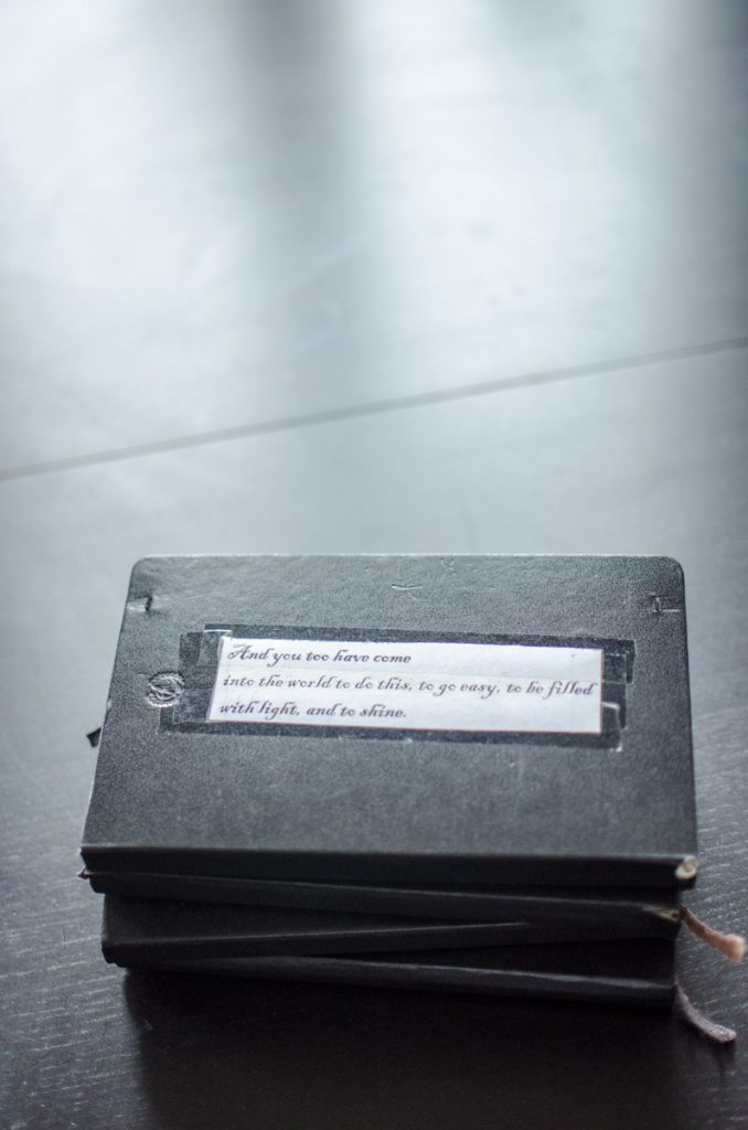 Stack of Moleskin journals with quote