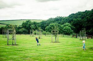 Boys running through the orchard in Devon