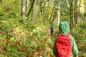 Boy walking in woods with Fjallraven backpack