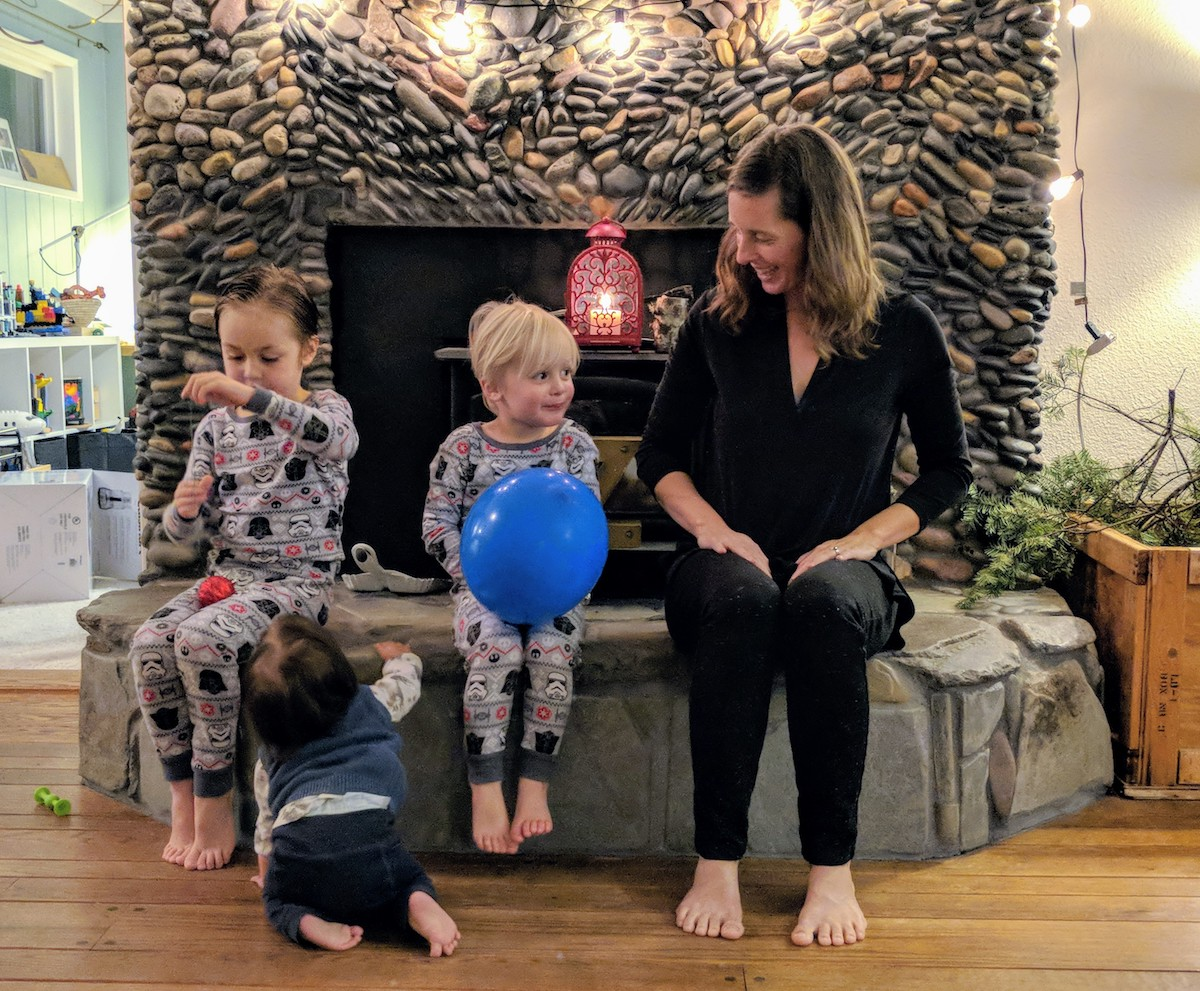 Jodi with babies at fireplace