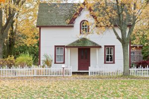 White house with white fence in autumn
