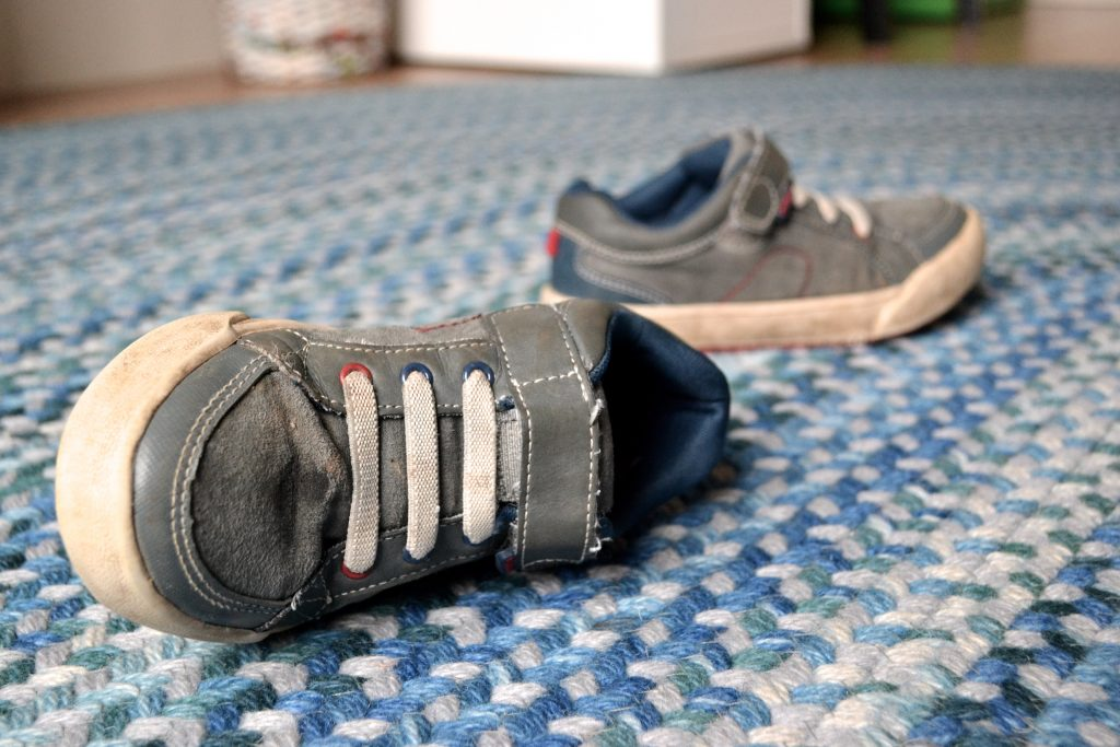 A pair of toddler's shoes tossed onto a braided blue rug.