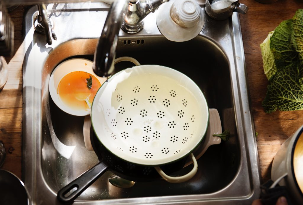 A stainless steel kitchen sink filled with a beautiful mess of dishes.