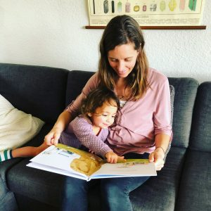 Exhausted mother reading with baby daughter